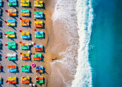 Aerial view of lying woman on the sandy beach with colorful chaise-lounges. Young woman on the sea at sunset in Europe. Top view. Landscape with girl on the seashore, blue water and waves. Resort